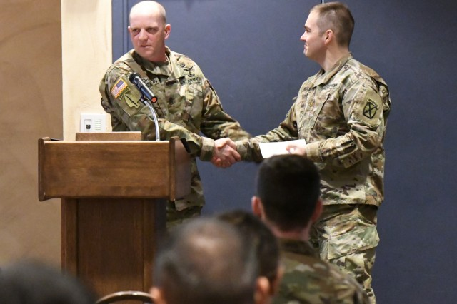 Command Sgt. Maj. Jason Johnson concludes his remarks at the Fort Drum Army Emergency Relief campaign kickoff Feb. 19 by presenting his AER contribution to Maj. Andrzej Kujawski, a 10th Mountain Division AER campaign coordinator. (Photo by Mike Strasser, Fort Drum Garrison Public Affairs)