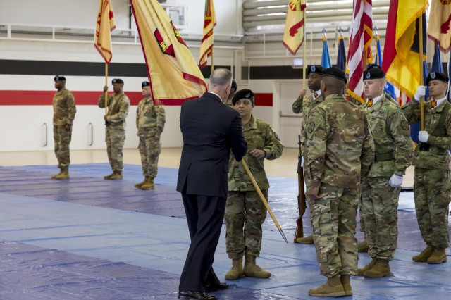 Michael Formica, director of IMCOM-Europe, passes the organization's guidon to incoming Command Sgt. Maj. Samara Pitre during a change-of-responsibility ceremony held Feb. 21 at Sembach, Germany.