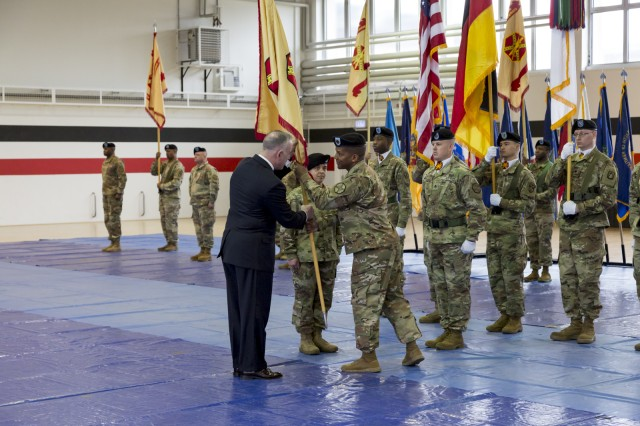 Outgoing IMCOM-Europe Command Sgt. Maj. Ulysses Rayford passes the organization's guidon to Michael Formica, director of IMCOM-Europe, during a change-of-responsibility ceremony held Feb. 21, 2019 at Sembach, Germany.
