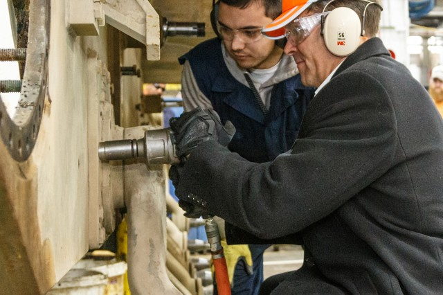 Secretary of the Army Mark T. Esper operates an impact wrench to remove bolts from a M1 Abrams tank in Anniston Army Depot's Combat Vehicle Repair Facility during his Feb. 20 tour of the installation.