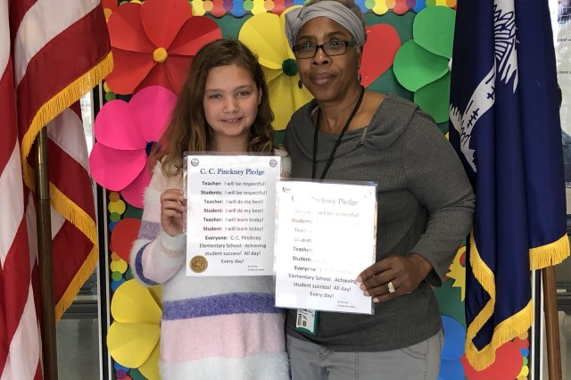 Evie Ford, third grade student at C.C. Pinckney Elementary school, holds the new school pledge that she wrote, side-by-side with principal Theresa Harvey. Ford's piece was selected to be the one-and-only C.C. Pinckney pledge out of nearly 300 student entries. It stood out as the only entry that incorporated both staff and students.