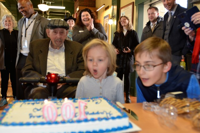 Retired Col. George Westlake watches as his great grandson, Roman Rehn, center-right, 4, and great-great grandson, Jaden George, right, 10, blow out the birthday candles at the Lewis Army Museum Feb. 21.