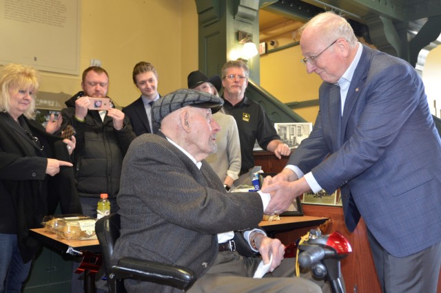 Retired Maj. Gen. James Collins, right, a former I Corps deputy commanding general and chief of staff who is now a civilian aide to the secretary of the Army, presents his coin to retired Col. George Westlake at the Lewis Army Museum Feb. 21.