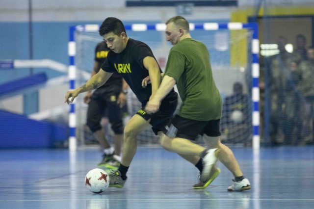 SKWIERZYNA, Poland (Feb. 21, 2019) -- A U.S. and Polish player battle for the ball during  a friendly futsal game between Soldiers from 101st Brigade Support Battalion, 1st Armored Brigade Combat Team, 1st Infantry Division, and Polish soldiers, here, Feb. 21. Futsal is a variation of standard outdoor soccer, played on a hard court and typically indoors. (U.S. Army photo by Sgt. Thomas Mort)