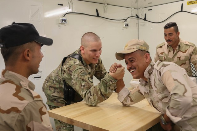 U.S. Army Staff Sgt. David Johnson, the powertrain shop chief assigned to B. Company, 935th Aviation Support Battalion, Illinois Army National Guard, arm-wrestles with an Iraqi aviation engineer during a break from organizing the portable maintenance shop containers at an Iraqi hangar at Camp Taji Military Complex, Oct. 1, 2018. The Iraqi Air Enterprise will ultimately provide Iraq with the self-sufficient air capabilities required by a sovereign nation to protect its borders and defeat internal threats.