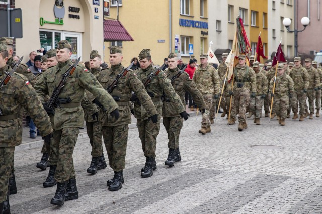 SKWIERZYNA, Poland (Feb. 23, 2019) — A platoon of Soldiers from 101st Brigade Support Battalion, 1st Armored Brigade Combat Team, 1st Infantry Division, march to their position during a ceremony in support of 61 Polish cadets taking an oath to defend and serve their country, in the town center. (U.S. Army photo by Sgt. Thomas Mort)