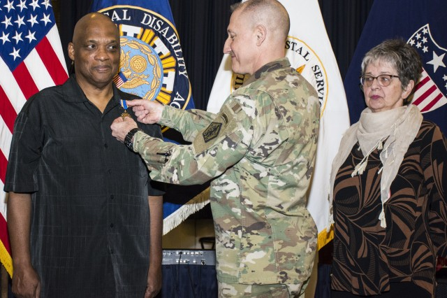With wife Rita by his side, Vietnam War veteran and Radcliff, Ky. resident Sgt. 1st Class James Hicks (retired) is officially presented the Air Medal Feb. 22, 2019, by Brig. Gen. Robert Bennett, the Adjutant General of the U.S. Army and executive director of Military Postal Service Agency.