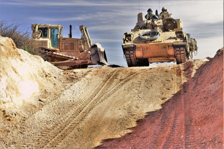 """After the armored bulldozers dig enough into the earth, a test must be conducted to ensure that the Bradley fighting vehicle is concealed and able to maneuver freely at the Fort Bliss Training Area, N.M., Feb. 8. """"Old Reliable"""" drives into the ditch calculating the amount of room on both sides as well as the amount of top coverage."""