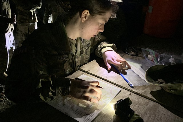Spc. Esther Alger, the 2019 Virginia National Guard Soldier of the Year, plots points on the map during the land navigation portion of the 2019 Virginia National Guard Best Warrior Competition Feb. 22, 2019, at Fort Pickett, Virginia. (U.S. National Guard photo by Cotton Puryear)
