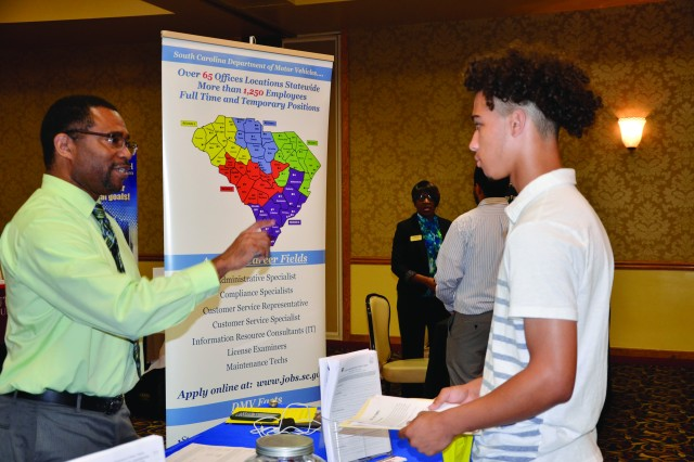 Curtis Price, human resources manager with the S.C. Department of Motor Vehicles, speaks with Jonathan Lovett about open temporary positions with S.C. DMV during the Army Community Service Teen Job and Education Fair last year at the Fort Jackson NCO Club.