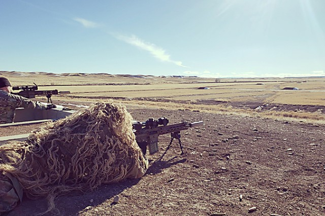 A test Sniper engages targets identified by his spotter while wearing a Ghillie suit during the Compact, Semi-Automatic Sniper Rifle (CSASS) operational test at Fort Carson, Colo.