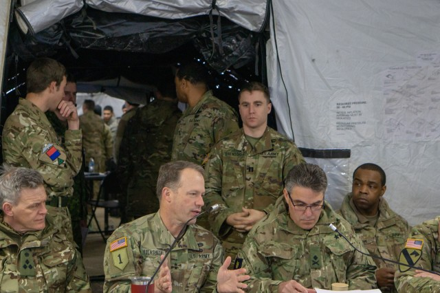 """Maj. Gen. John S. Kolasheski (second from left), the 1st Infantry Division commanding general, briefs Brig. Mark Pullan, commander of the 1st (United Kingdom) Artillery Brigade; Maj. Gen. James Swift, the 3rd (United Kingdom) Division commanding general; and Brig. Gen. Matthew Van Wagenen, 3rd (UK) Div. Deputy commander, on the inner workings of the """"Big Red One's"""" joint operations center Feb. 28, 2019, at Fort Riley, Kansas. Leaders from the two divisions met during the 1st Inf. Div.'s recent command post exercise as they prepare for Warfighter 19-04."""
