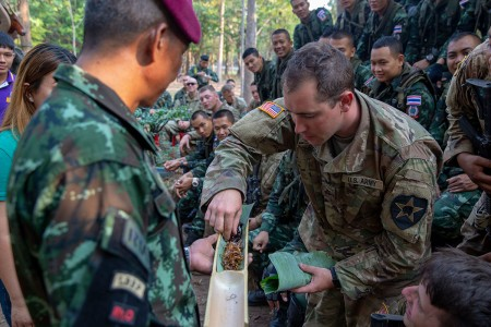 Royal Thai Armed Forces Master Sgt. 1st Class. Saengchai Seeuthai, left, passes various insects as food to U.S. Army Pfc. Kyle Ridge, a combat medic with Bravo Company, 5th Battalion, 20th Infantry Regiment, during exercise Cobra Gold 19 at Phitsanulok, Kingdom of Thailand, Feb. 13, 2019. Cobra Gold is one of the largest theater security cooperation exercises in the Indo-Pacific and is an integral part of the U.S. commitment to strengthen engagement in the region.