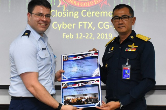 Maj. Jason Silves, plans officer with the 262nd Cyberspace Operations Squadron and exercise director, is presented a certification of participation during the first-ever cyberspace field training exercise as part of Exercise Cobra Gold in Bangkok, Kingdom of Thailand, Feb. 21, 2019.