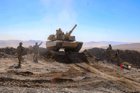 Soldiers guide an M1A2 Abrams tank through the breach point while conducting a live-fire exercise during Decisive Action Rotation 19-03 at the National Training Center, Fort Irwin, Calif., Jan. 23, 2019. Decisive Action Rotations at the NTC ensure Army Brigade Combat Teams remain versatile, responsive, and consistently available for current and future contingencies.