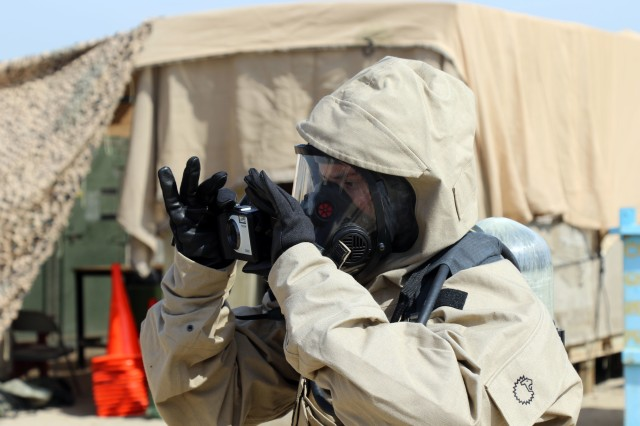 Sgt. Amanda Plummer, of the 637th Chemical Company, takes photos as part of the standard protocol while entering a contaminated area during a demonstration on Feb. 14, 2019, at Camp Arifjan, Kuwait. Soldiers from the unit assigned to Task Force Spartan provide a display on the chemical, biological, radiological, and nuclear-dismounted reconnaissance equipment to Kuwait Weapons of Mass Destruction Defense Command. The unit is deployed to Kuwait as the CBRN defense response force for the U.S. Central Command area of responsibility.