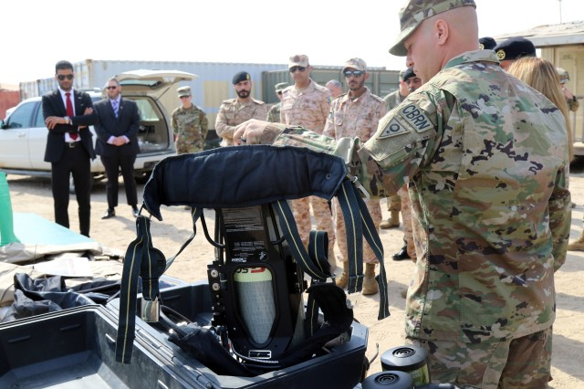 Staff Sgt. Dustin Bowshier of the 637th chemical, biological, radiological and nuclear Company is the Non-Commissioned Officer in Charge and explains the self-contained breathing apparatus that is worn with the suits for different levels of contamination during the display on the CBRN dismounted reconnaissance equipment on Feb. 14, 2019, at Camp Arifjan, Kuwait. Soldiers from the unit provide an array of layout and equipment with CBRN dismounted reconnaissance equipment to Kuwait Weapons of Mass Destruction Defense Command. The 637th Chemical Company is deployed to Kuwait as the CBRN defense response force for the U.S. Central Command area of responsibility.