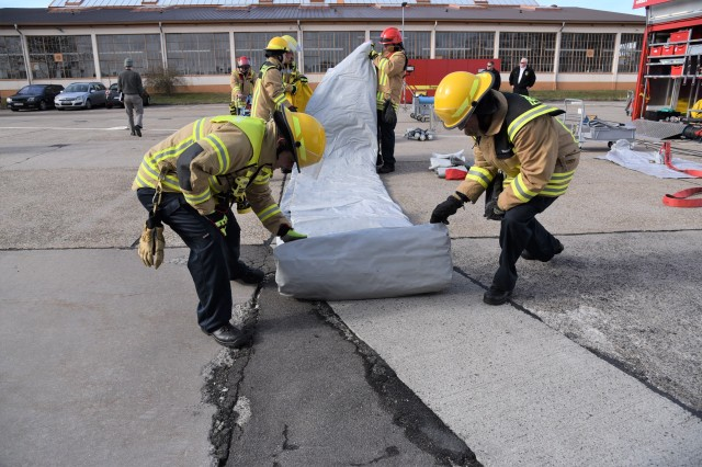 U.S. Army Garrison Rheinland-Pfalz firefighters roll out a tent to be used for personnel decontamination. Garrison firefighters and members of the 773rd Civil Support Team demonstrated their capabilities to foster interoperability at Sembach Kaserne, March 6.