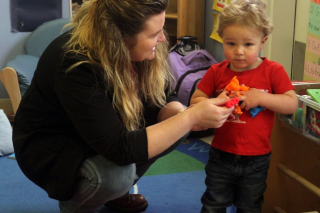 Melissa Myers, director of Cooper Child Development Center, helps 2-year-old Carter choose a toy to play with at the center.