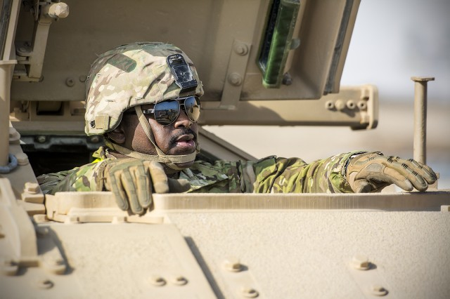 Spc. Terry Williams, a Bradley Fighting Vehicle driver assigned to C. Company, 2nd Battalion, 198th Armor Regiment, prepares to move his vehicle to an Army Prepositioned Stock-5 warehouse at Camp Arifjan, Kuwait, Feb. 25. The vehicles are part of APS-5's ABCT equipment set. APS-5 is managed and maintained by the 401st Army Field Support Brigade. (U.S. Army photo by Justin Graff, 401st AFSB Public Affairs)