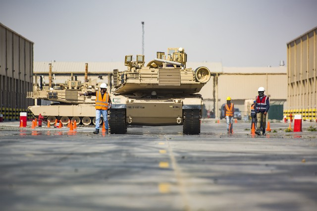 Contractors supporting the Army Field Support Battalion-Kuwait guide M1A2 Abrams Tanks into Army Prepositioned Stock-5 warehouses at Camp Arifjan, Kuwait, Feb. 26. (U.S. Army Photo by Justin Graff, 401st AFSB Public Affairs)