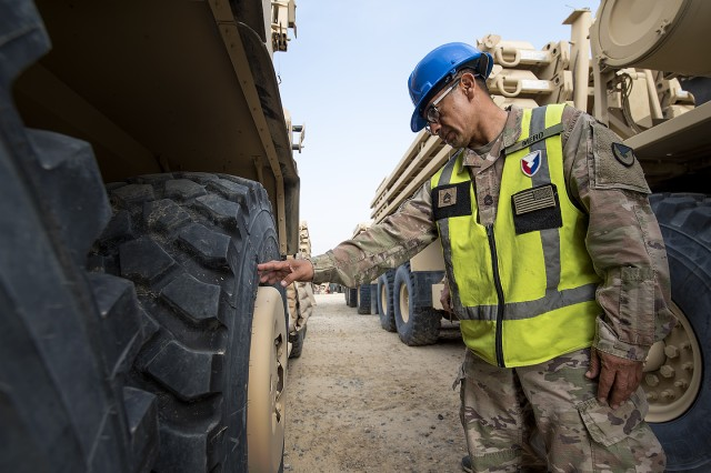 Sgt. 1st Class Antonio Mero, quality assurance specialist, Army Field Support Battalion-Kuwait examines a damaged tire during a joint technical inspection at a remote Army Prepositioned Stock-5 staging lot at Camp Arifjan, Kuwait, Feb. 23. The vehicles are part of APS-5's Armored Brigade Combat Team equipment set. APS-5 is managed and maintained by the 401st Army Field Support Brigade. (U.S. Army photo by Justin Graff, 401st AFSB Public Affairs)
