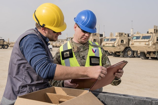 Staff Sgt. Class Joshua Borst (right), quality assurance specialist, Army Field Support Battalion-Kuwait verifies vehicle maintenance packets at a remote Army Prepositioned Stock-5 staging lot at Camp Arifjan, Kuwait, Feb. 23. The vehicles are part of APS-5's Armored Brigade Combat Team equipment set. APS-5 is managed and maintained by the 401st Army Field Support Brigade. (U.S. Army photo by Justin Graff, 401st AFSB Public Affairs)