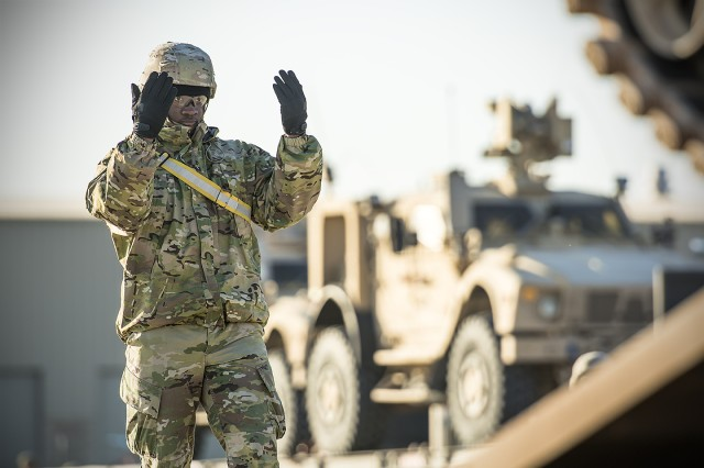 A Soldier assigned to the 155th Armored Brigade Combat Team guides a vehicle off of a trailer at an Army Prepositioned Stock-5 staging area at Camp Arifjan, Kuwait, Feb. 21. The vehicles are part of APS-5's ABCT equipment set. APS-5 is managed and maintained by the 401st Army Field Support Brigade. (U.S. Army Photo by Justin Graff, 401st AFSB Public Affairs)
