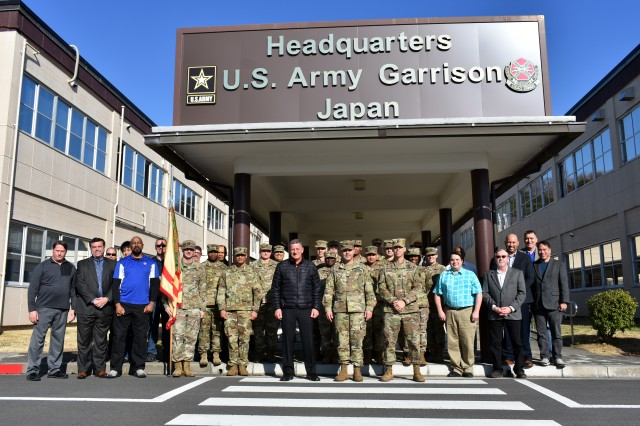 U.S. Army Garrison Japan Soldiers and civilians pose for a photo at garrison headquarters at Camp Zama, Japan, March 8 to commemorate the garrison's command change to U.S. Army Materiel Command. Col. Phillip Gage, commander, USAG Japan, stands center. USAG Japan Command Sgt. Maj. Billy Norman stands to Gage's left, and Steve Niederriter, deputy garrison commander, stands to Gage's right.