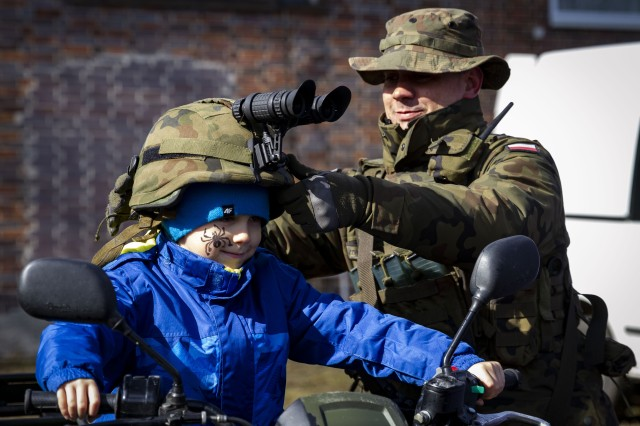 A Polish soldier gives a young local resident the opportunity to sit on a Polish military four wheel all-terrain vehicle, during Poland's 20 year anniversary celebration to recognize Poland's accession to NATO in 1999, here, Mar. 8, 2019. The event was open to the public as approximately 1,000 locals were in attendance to visit and learn about the Polish and American militaries.