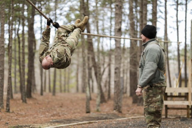 Sgt. Gary Payne, with the North Carolina National Guard's 694th Supply Maintenance Company, 113th Sustainment Brigade, pulls himself along a rope while his sponsor, Staff Sgt. Joshua Covington, also with the 694th, encourages him during the obstacle course at the North Carolina Best Warrior Competition March 5, 2019, at the Camp Butner Training Center in Stem, N.C.