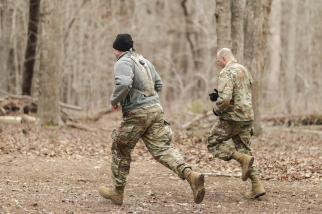 Sgt. Gary Payne, right, with the North Carolina National Guard's 694th Supply Maintenance Company, 113th Sustainment Brigade, runs to the next obstacle while Staff Sgt. Joshua Covington, also with the 694th, runs next to him while shouting encouragement during the obstacle course at the North Carolina Best Warrior Competition March 5, 2019, at the Camp Butner Training Center in Stem, N.C.