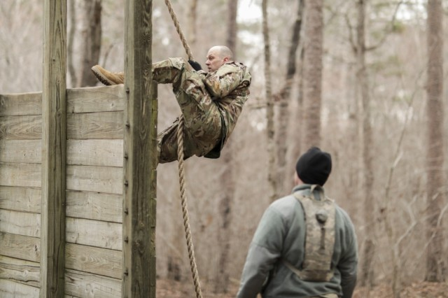 Sgt. Gary Payne, with the North Carolina National Guard's 694th Supply Maintenance Company, 113th Sustainment Brigade, uses a rope to climb a wall while his sponsor, Staff Sgt. Joshua Covington, also with the 694th, encourages him during the obstacle course at the North Carolina Best Warrior Competition March 5, 2019, at the Camp Butner Training Center in Butner, N.C.