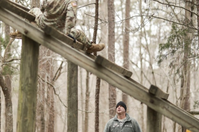 Spc. Lynn Cox, with the North Carolina National Guard's 626th Supply Maintenance Company, 113th Sustainment Brigade, navigates over, then under, wood beams during the obstacle course while her sponsor, Staff Sgt. Donald Hill, also with the 626th, guides and encourages her, at the North Carolina Best Warrior Competition March 5, 2019, at the Camp Butner Training Center in Stem, N.C.