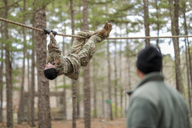 Spc. Lynn Cox, with the North Carolina National Guard's 626th Supply Maintenance Company, 113th Sustainment Brigade, pulls herself along a rope while her sponsor, Staff Sgt. Donald Hill, also with the 626th, encourages her during the obstacle course at the North Carolina Best Warrior Competition March 5, 2019, at the Camp Butner Training Center in Stem, N.C. The competition, held March 4-7, 2019, tests the mental and physical strength of enlisted Soldiers and Noncommissioned Officers through several events including an Army physical fitness test, a 12-mile ruck march, an obstacle course, an essay, weapon qualification, and many other events.