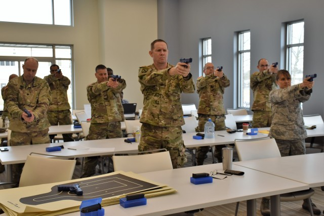 Military officers with the U.S. Army Medical Materiel Development Activity practice their shooting stance at Heritage Training and Shooting Center in Frederick, Maryland.