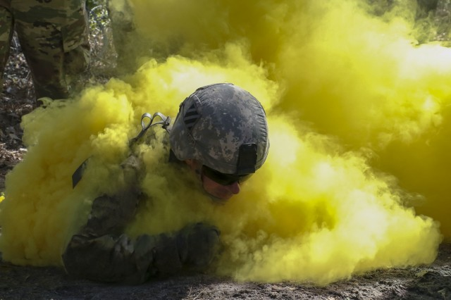 Georgia National Guardsman, Sgt. Matthew Taylor, representing the Columbus-based 648th Maneuver Enhancement Brigade, low crawls through the smoke during the Individual Movement Technique event at the state Best Warrior Competition at Fort Stewart, Georgia on March 6, 2019. Competitors were evaluated on time to complete the course, their capability to move through various obstacles and the clearing of a bunker.