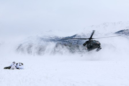Paratroopers huddle over a mock casualty to protect it from the rotor-wash of a landing UH-60 helicopter at Joint Base Elmendorf-Richardson, Alaska, Feb. 20, 2019.