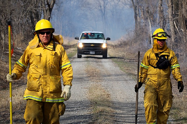 Todd Mitchell (left) and Joseph Whitman with the U.S. Army Corps of Engineers, Tulsa District walk the roadway monitoring fire during a prescribed burn training class March 4-8, 2019, at Ft. Gibson Lake near Okay, Okla. The training class is an annual event in its 11th year and teaches natural resource specialists and lake maintenance staff how to properly and safely conduct a burn.