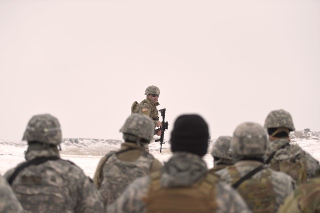 Sgt. Sol Griffith, a fire team leader, assigned to the Wyoming Army National Guard's C Company, 1st Battalion, 297th Infantry Regiment (Forward), addresses his comrades following a demonstration of the proposed new rifle marksmanship evaluation. The deploying infantry unit was the first to try out the new test at Camp Guernsey, during mobilization training March 7, 2019.