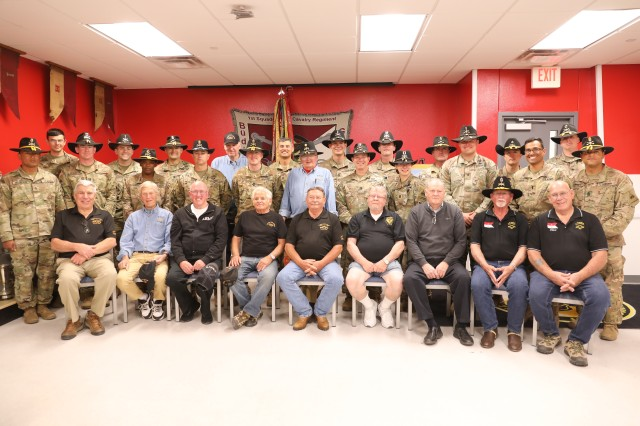 Soldiers with 1st Squadron, 1st Cavalry Regiment pose with Vietnam Veterans during a reunion at the squadron's headquarters March 8 at Fort Bliss, Texas. During their visit, the unit dedicated a painting donated from the family of Command Sgt. Maj. Gary Boggs who served with the 1-1 CAV during the Vietnam War.