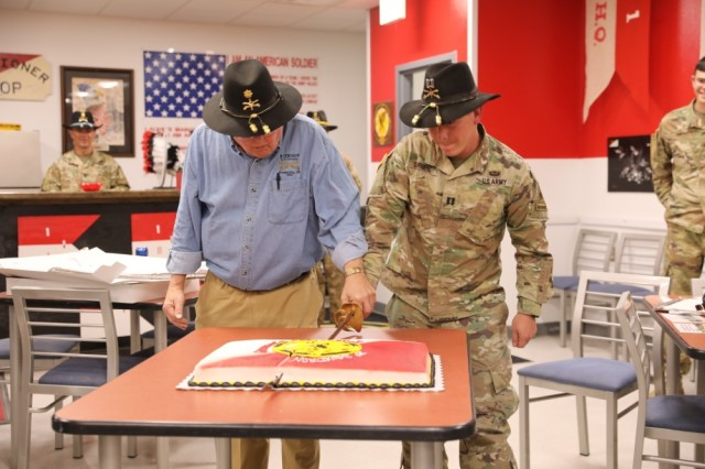 "From Left to Right: Retired Maj. Walter Reed and Capt. Bryan Uribe, the former and present day commander of Bravo Troop ""Bandits"", 1- CAV cut a cake with a saber March 8 at Fort Bliss, Texas. This moment signifies the legacy of the unit and its rich tradition."
