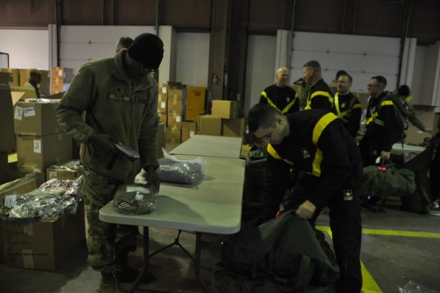 Pvt. Cheyenne Rivera, B Battery, 4th Battalion, 3rd Air Defense Artillery, puts Extended Cold Weather Clothing System gear into his bag as Spc. Tyrone Payne, E Battery, 3-2nd ADA, checks off Rivera's list, during the Rapid Fielding Initiative, Feb. 6, 2019, at Fort Sill.