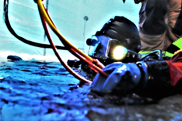 A firefighter wearing a full diving suit and related equipment treads water prior to diving under the ice Feb. 6, 2019, at Big Sandy Lake on South Post at Fort McCoy, Wis. About a dozen firefighters with the Directorate of Emergency Services Fire Department practiced ice diving as part of the Fort McCoy dive team. Overall, the firefighters completed four days of training related to ice diving that also included classroom time and practice at the pool at Rumpel Fitness Center. Fort McCoy built the dive team capability eight years ago and the team has responded to real-world emergencies, including recently to an emergency in Sparta, Wis. (U.S. Army Photo by Scott T. Sturkol, Public Affairs Office, Fort McCoy, Wis.)
