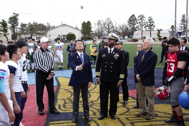 Former Japanese Prime Minister Taro Aso makes the coin toss at the start of the eighth annual Tomodachi Bowl March 10 at Naval Air Facility Atsugi, Japan's Reid Stadium. Naval Air Facility Atsugi Commander Capt. Lloyd Mack stands next to him.