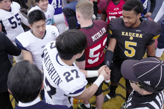 Kadena High School's Eric McCarter, right, shakes hands with Gakushin University's Riku Koyama prior to the start of the eighth annual Tomodachi Bowl March 10 at Naval Air Facility Atsugi's Reid Stadium. The Tomodachi Bowl is an annual exhibition football game between Department of Defense Dependents Schools-Pacific high school players from Japan, Korea and Guam, and Japanese first-year college players.