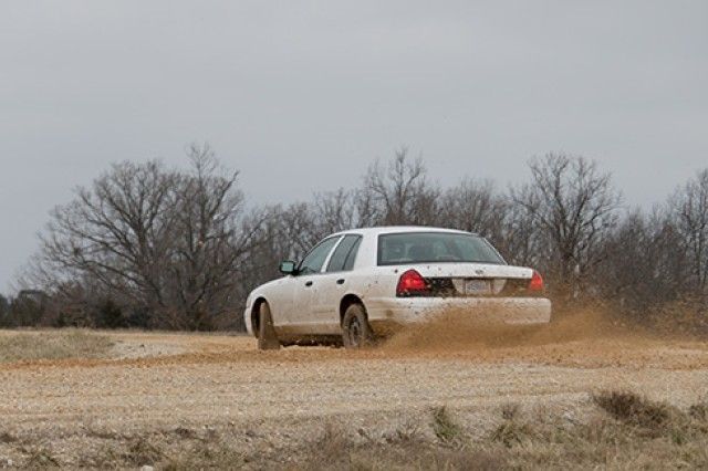 A driver takes a fast turn on the dirt road at the Anti-terrorism Evasive Driving course.