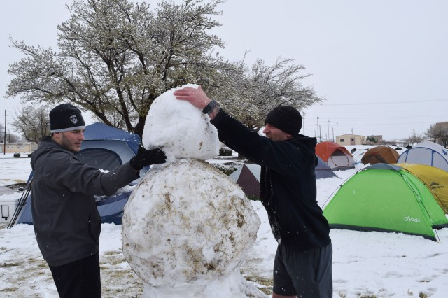 Johnny Bryant (left) and Nick Cox steady the head to their snowman.