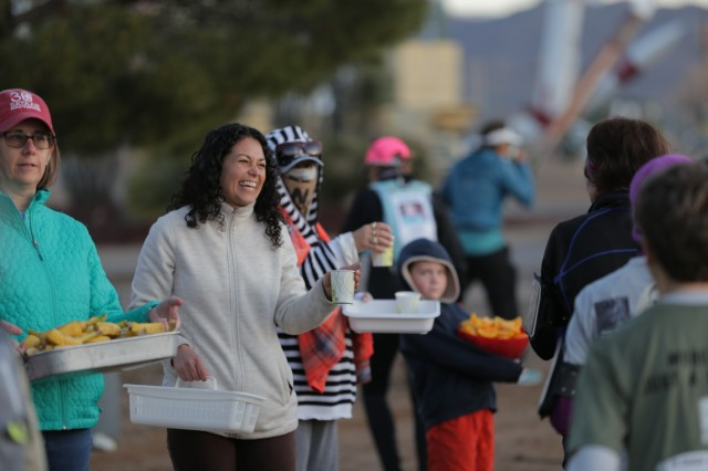 "U.S. Rep. Xochitl Torres Small (D-N.M.) offers water to marchers passing by Water Point 1 during the 2019 Bataan Memorial Death March held March 17, 2019, at White Sands Missile Range, N.M. Torres Small joined volunteers offering water, bananas and orange slices to a record 8,689 marchers from 50 states and 12 countries at the march honoring servicemembers subjected to the Bataan Death March. ""It is great to see the positivity of everyone involved here, and it's uplifting to see how this pulls the whole community together,"" said Torres Small."