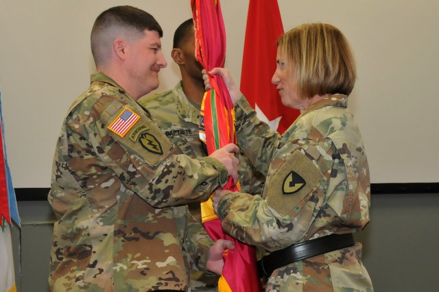 Brig. Gen. Michelle M.T. Letcher passes the Joint Munitions Command colors to incoming Command Sgt. Maj. Brian J. Morrison, during the Assumption of Responsibility Ceremony, March 18.